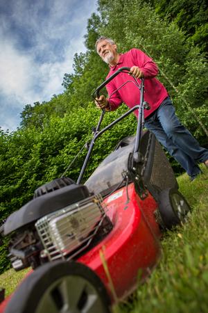 Lterer Mann , der den Rasen in seinem Garten mähen Standard-Bild - 93155104