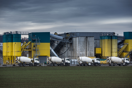 Concrete production plant/factory with  Concrete mixing transport trucks in front of it