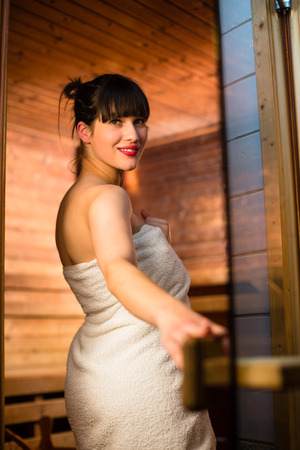 Young woman relaxing in a sauna, taking a break from her busy schedule, taking care of herself, enjoying the wellness benefits her job provides Standard-Bild