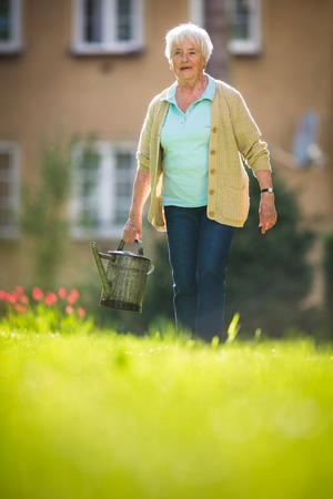 Senior woman doing some gardening in her lovely garden Standard-Bild