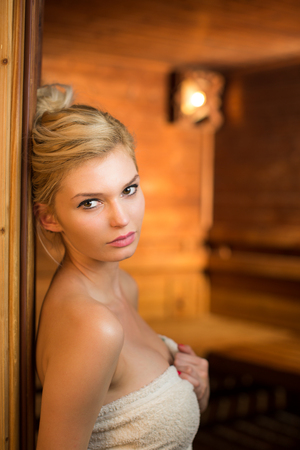 Attractive young woman relaxing in a sauna