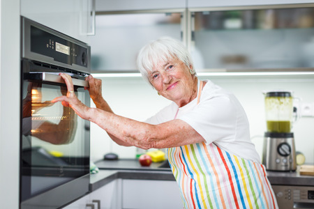Senior woman cooking in the kitchen - eating and cooking healthy for her family; putting some potatoes in the oven, enjoying active retirement Standard-Bild