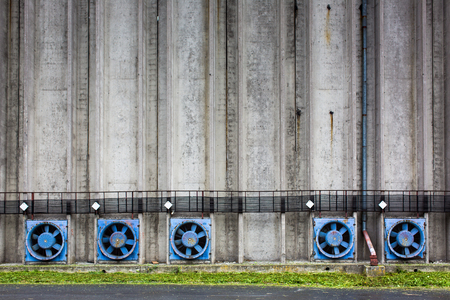 Conrete wall of a cereal silo tower with vents Stock Photo