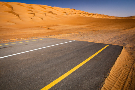 Modernity versus nature concept - end of civilisation, beginning of desert. Modern paved highway ending up in sand dunes.