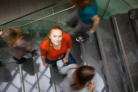 At the universitycollege - Students rushing up and down a busy stairway - confident pretty young female student looking upwards (color toned image)
