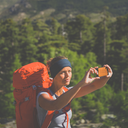 Pretty, female hiker in high mountains packing her backpack