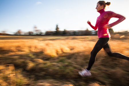 Young woman running outdoors on a lovely sunny winterfall day (motion blurred image)