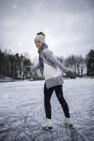 Young woman ice skating outdoors on a pond on a freezing winter day (color toned image; motion blurred image) Foto de archivo