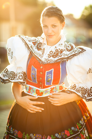 Keeping tradition alive: young woman in a richly decorated ceremonial folk dress/regional costume (Kyjov folk costume, Southern Moravia, Czech Republic) Imagens - 95056839