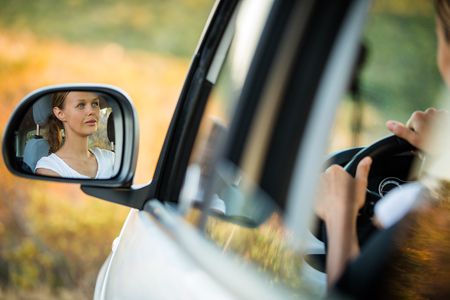 Pretty, young woman  driving her car - reflection in the side mirror (shallow DOF; color toned image)