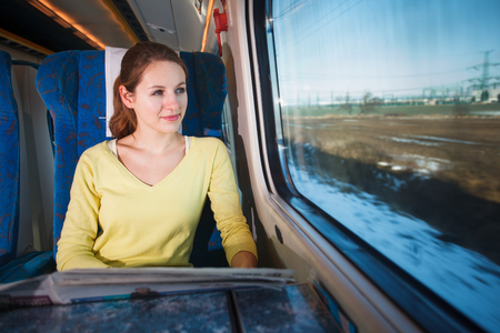 Young woman traveling by fast moving train - looking at the motion blurred landscape passing by