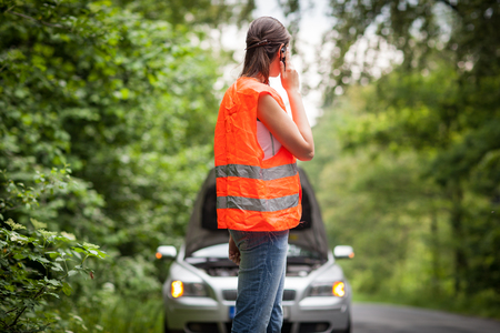 Young female driver wearing a high visibility vest, calling the roadside serviceassistance after her car has broken down Banque d'images