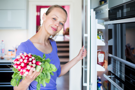 Pretty, young woman taking fresh vegetables from her fridge - being on a gluten free vegan diet does not seem to be a problem for her (shallow DOF; color toned image) Banco de Imagens