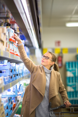 Beautiful young woman shopping for groceries and fruits and vegetables in produce department as well as some lactose free diary products in a modern grocery storesupermarket (color toned image; shallow DOF)