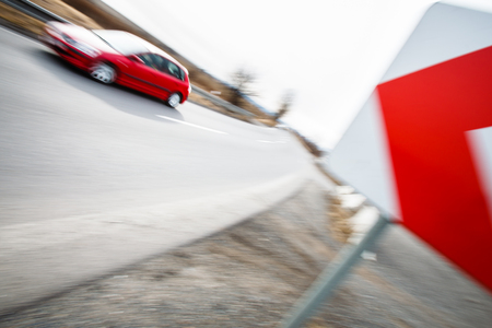Traffic concept: car driving fast through a sharp turn (motion blur is used to convey movement)