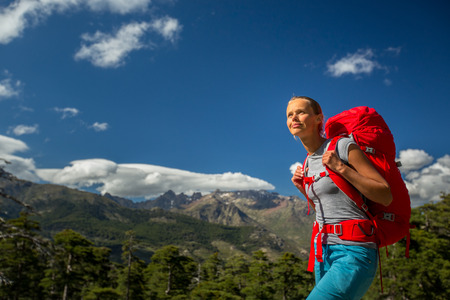 Pretty, female hiker in high mountains with her giant backpack, getting ready for some hiking