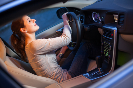Pretty young woman driving her new car Banco de Imagens
