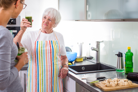 Senior womangrandmother cooking in a modern kitchen (shallow DOF; color toned image)