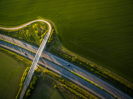 Aerial view of a highway amid fields with cars on it Stock Photo - 96357215