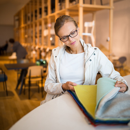 Pretty young woman  choosing the right materialcolor for her modern appartement interior (shallow DOF; color toned image)