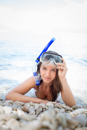 Pretty, young woman on a beach during her summer vacation with snorkel lying on beach with snorkeling mask and fins smiling happy enjoying the sun on a sunny summer day.