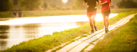 Couple running outdoors, at sunset, by a river, staying active and fit Banco de Imagens