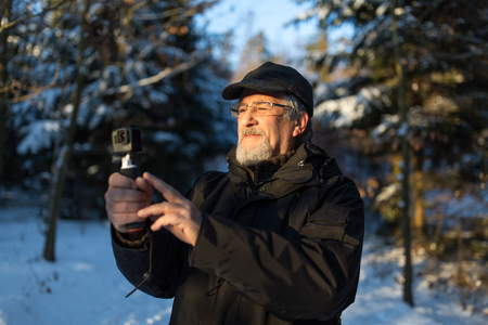 Handsome senior man shotting video with his adventura outdoor camera on a grip handle outdoors on a lovely winter day, enjoying retirement Standard-Bild - 102164443