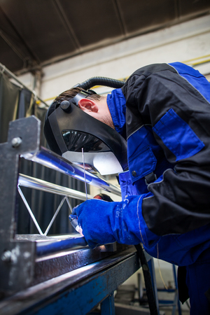 Welder working a welding metal with protective mask and sparks Stock Photo