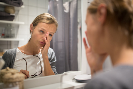 Groggy, young woman yawning in front of her bathroom mirror in the morning - trying to wake up and get ready for work Reklamní fotografie