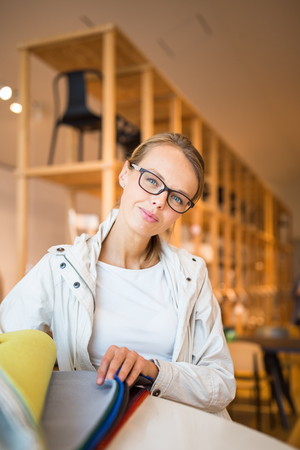 Pretty young woman choosing the right materialcolor for her modern apartment interior