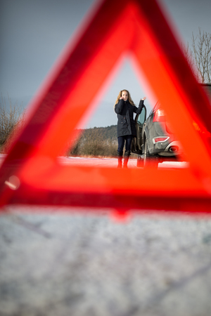 Realy angry young woman in a road distress situation - setting up a warning triangle and calling for assistance after her car broke down in the middle of nowhere on a freezing winter day