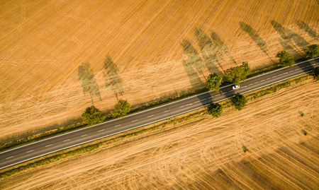 Aerial view of a country road amid fields with a car on it