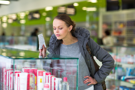 Young woman blowing her nose while in a modern pharmacy, choosing pills to help her with the flu/cold