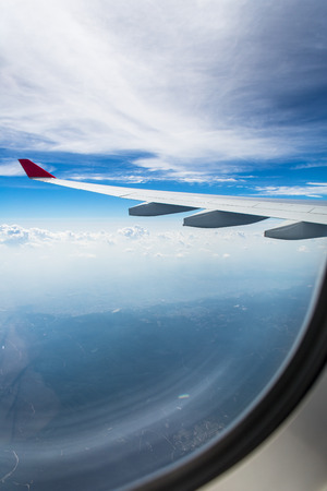 An airplane wing through airplane window with blue sky background Stockfoto
