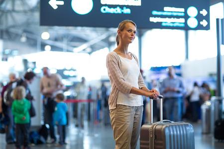 空港で若い女性の乗客,彼女の遅れたフライトを待っています