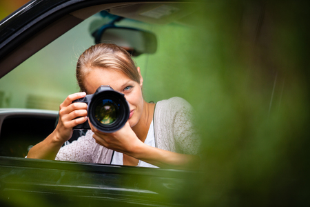 Female photographerpaparazzi taking pictures of a famous high-profile person from her car Stock Photo