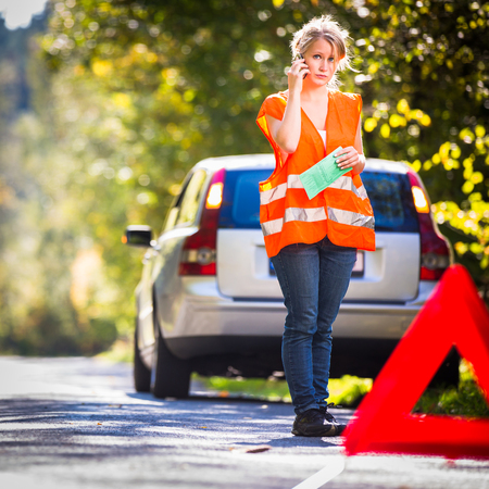 Young female driver wearing a high visibility vest, calling the roadside serviceassistance after her car has broken down Stock Photo