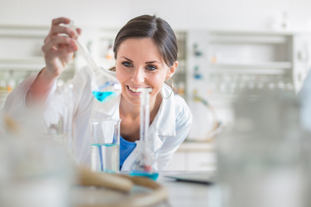 Young, female researcher carrying out experiments in a lab (shallow DOF; color toned image) Stock Photo