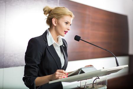 Bonita, joven mujer de negocios dando una presentación en una conferencia / reunión (DOF superficial; imagen en color entonado) Foto de archivo
