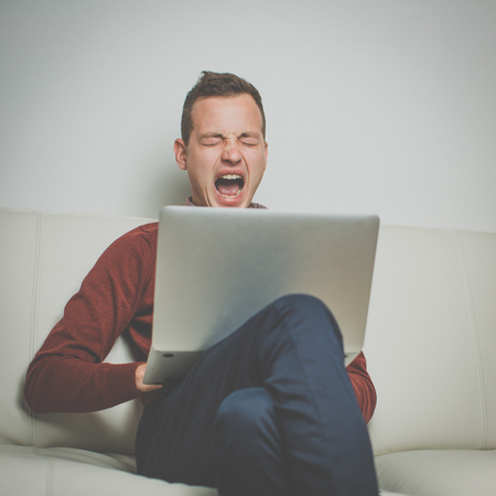 Sleepy young man sitting on a sofa and trying to get some work done on his laptop computer, yawning Stock Photo