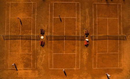 Aerial shot of a tennis courts with players in warm evening sunlight