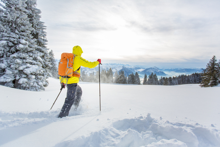 Young man snowshoeing in high mountains, enjoying splendid winter weather with abundance of snow Stock Photo