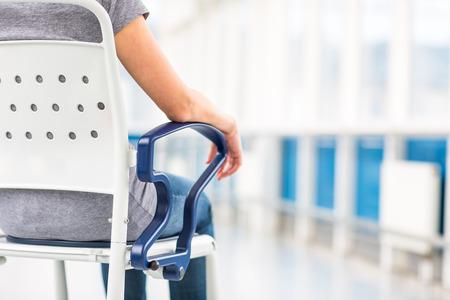 Paziente femminile, seduto su una sedia a rotelle per i pazienti che non si sentono abbastanza bene per stare in piedi, in attesa di essere curati in un ospedale moderno (DOF superficiale; immagine a colori dai toni) Archivio Fotografico - 99570779