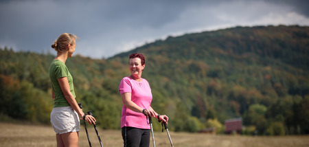 Pretty, young woman nordic walking on a forest path, taking in the fresh air, getting the daily dose of exercise
