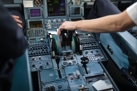 Pilots hand accelerating on the throttle in  a commercial airliner airplane flight cockpit during takeoff Stock Photo