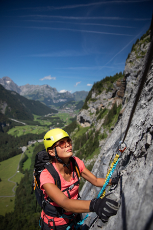 Pretty, female climber on a via ferrata - climbing on a rock in Swiss Alps Stock Photo