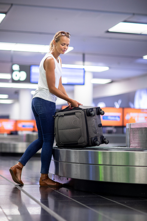 Man (traveler) picking up suitcase from baggage claim in airport terminal (color toned image; shallow DOF) Stock Photo