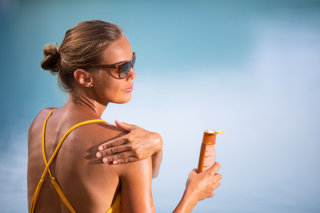 Suncream Concept. Pretty, young woman in a swimsuit is applying sunscreen trying to protect the skin from the harmful effects of sunlight she loves Stock Photo