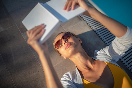 Young Beautiful Suntanned Woman wearing sunglasses relaxing next to a Swimming Pool  on a lovely Summer Day  - Reading a book 版權商用圖片