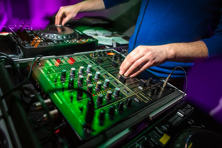 DJs hands at the music mixer at a party - playing some fine songs for the guests (color toned image)
